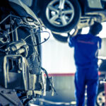Mechanic Working On Raised Vehicle